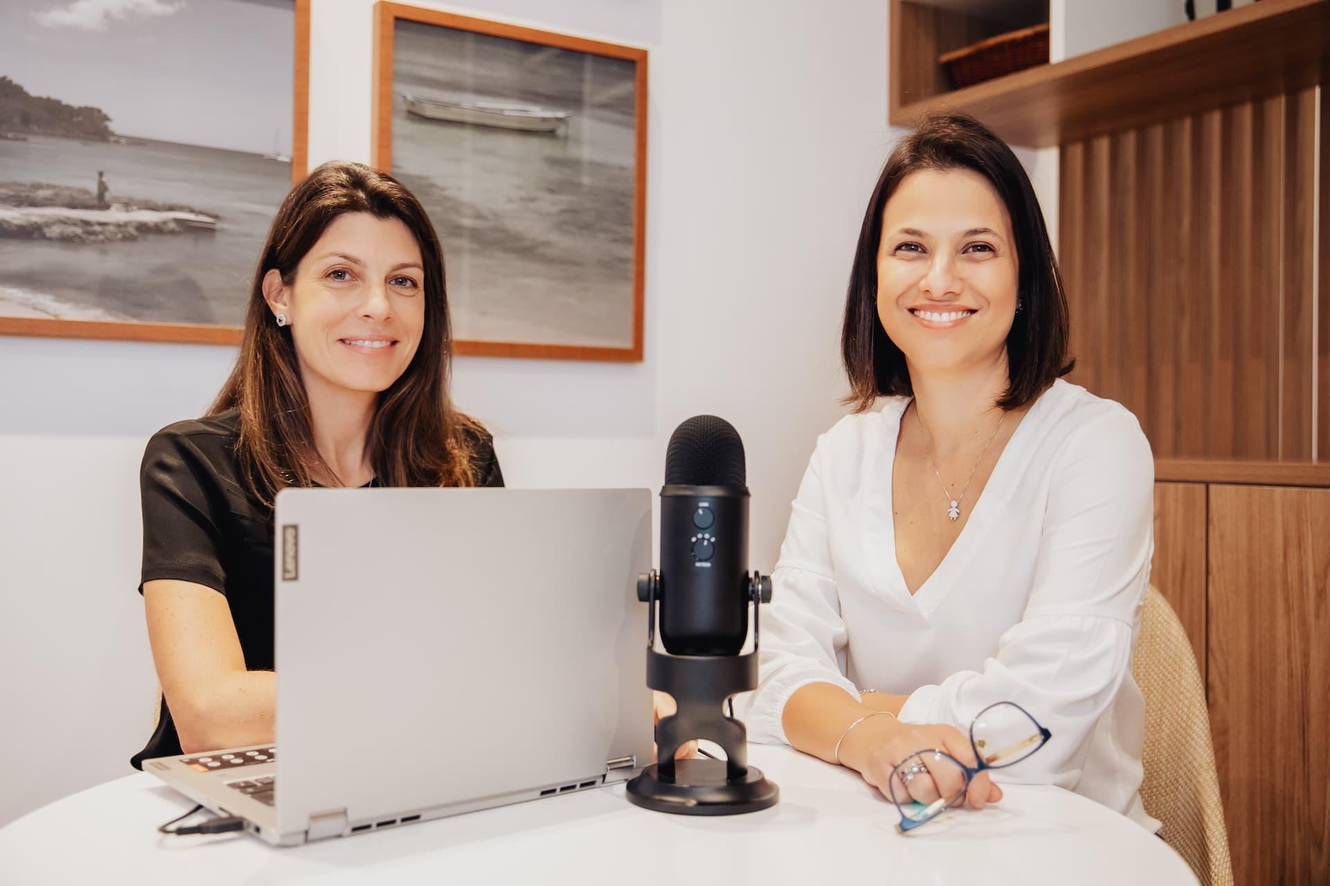 Carina e Cinthya numa mesa com um laptop e um microfone