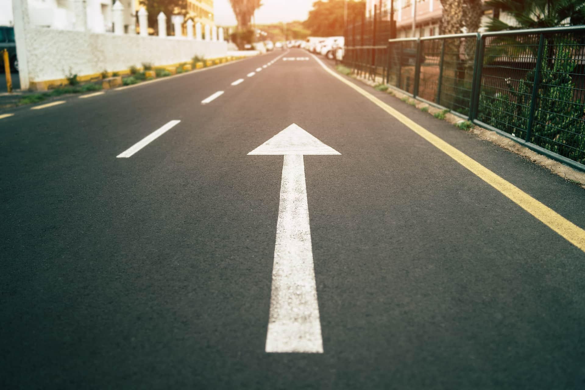 Seta branca para frente numa rua vazia